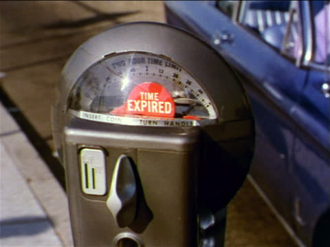 stockvideo's en b-roll-footage met 1962 pan from close up of expired parking meter to couple sitting in blue parked car on suburban street - passagiersstoel