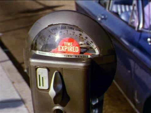 vídeos y material grabado en eventos de stock de 1962 pan from close up of expired parking meter to couple sitting in blue parked car on suburban street - menos de diez segundos