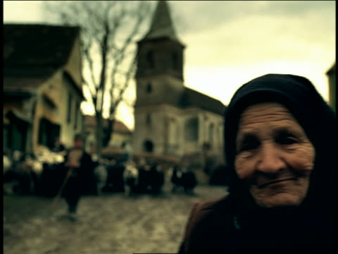 pan from close up portrait senior woman in native dress to herd of goats in road / sibiu, transylvania - transilvania video stock e b–roll