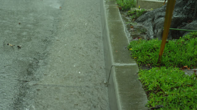 zoom out from close up to medium shot rain water flows in gutter during heavy rain in suburban neighborhood - gutter stock videos and b-roll footage