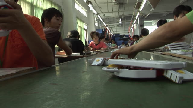 MS POV From conveyor belt as factory workers assemble toys and place them on belt/ Dongguan, China