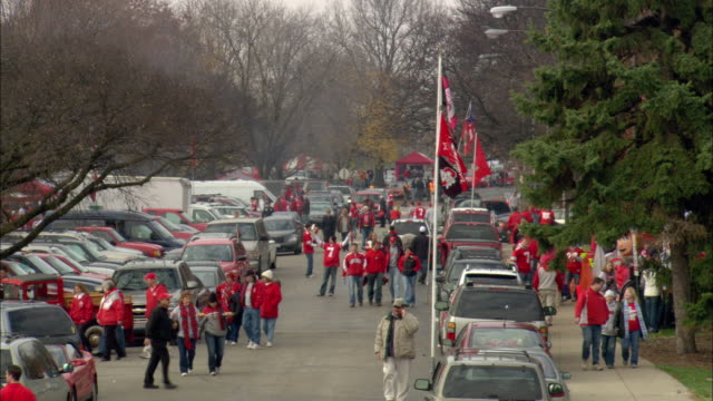 td from crosswalk sign to xws crowd of ohio state university college football fans walking campus sidewalk next to line of street lights parked cars... - ohio state university stock videos & royalty-free footage