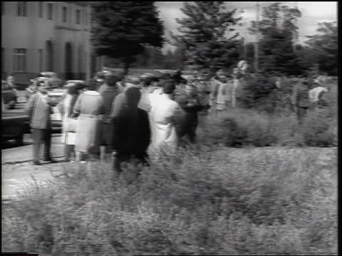 vídeos de stock, filmes e b-roll de pan from crowd of west germans to barbed wire fence of berlin wall / newsreel - fronteira internacional