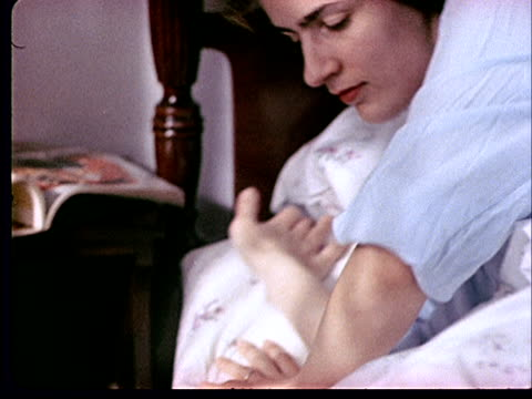 stockvideo's en b-roll-footage met 1962 ms pan from curtains to woman rising from bed and shaking her husband awake  - 1962