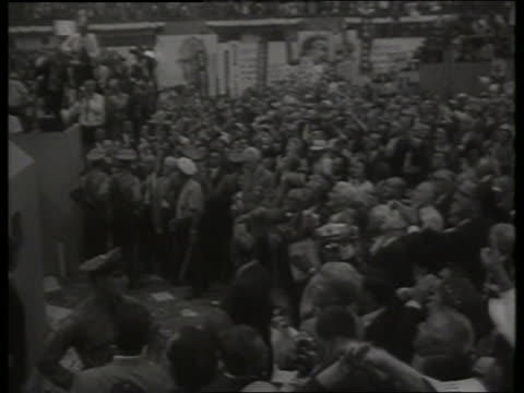 vídeos de stock, filmes e b-roll de b/w pan from democratic convention crowd to podium with lbj / 1960's / sound - 1964