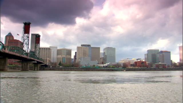 From downtown Portland cityscape mid highrise buildings to Hawthorne Bridge over Willamette River OR Columbia River