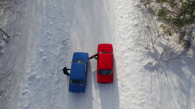 POV from drone of drivers getting into cars and racing on snow in forest