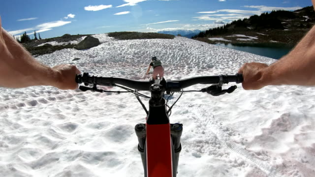 pov from e-bike of young woman descending steep snow slope with bicycle - ゲレンデ点の映像素材/bロール