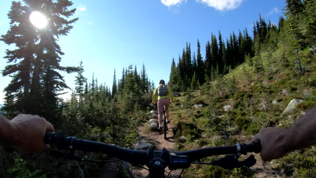 pov from e-bike of young woman traversing mountain trail - mountain bike stock videos & royalty-free footage
