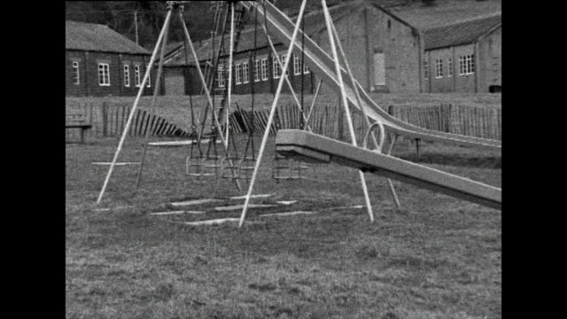 zo from empty playground with seesaw and swings; 1972 - part of a series stock videos & royalty-free footage
