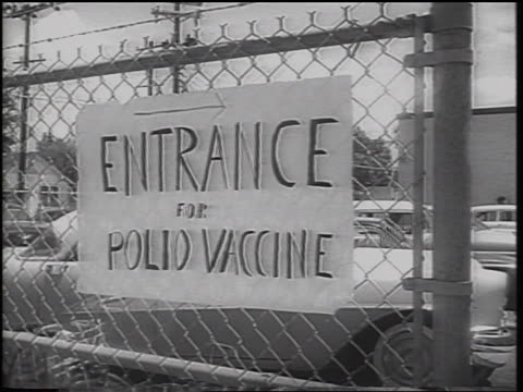 """from """"entrance for polio vaccine"""" sign on fence to people waiting in line / texas - polio stock videos & royalty-free footage"""