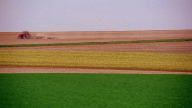 pan from farm tractor in field to line of trees / champagne, france - mellanstor grupp av objekt bildbanksvideor och videomaterial från bakom kulisserna