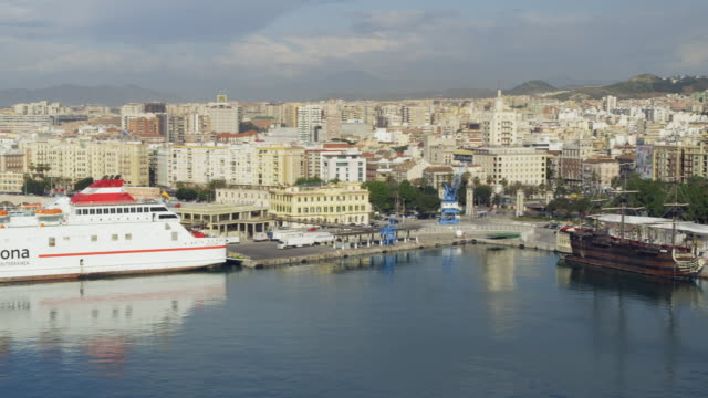 vídeos de stock e filmes b-roll de pan from ferry terminal (with the melilla ferry docked) via city center and cathedral to alcazaba fortress with town hall beneath it; old port and ships moored at quay number one in foreground / malaga, andalusia, spain - town hall