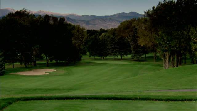 WS First hole fairway sloping green lined w/ trees Rocky Mountains distant BG OUT/IN FOCUS