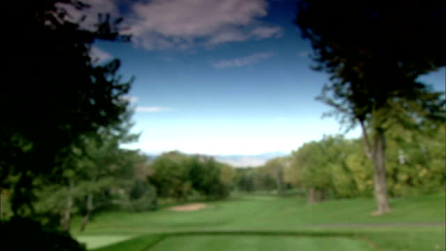 LS First hole fairway sloping green lined w/ trees Rocky Mountains distant BG OUT/IN FOCUS