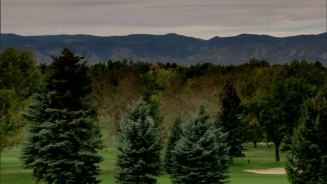 Trees first hole fairway and sloping green lined with more trees distant greenskeeper mowing fairway grass Rocky Mountains distant BG