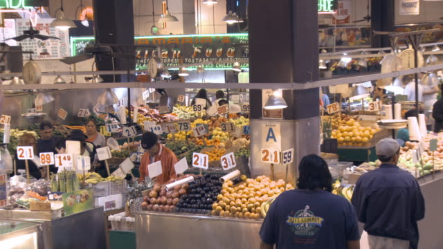 ZO from fruit and vegetable stands to WS of historic Grand Central Market on ground floor of Homer Laughlin Building /Los Angeles, California, USA