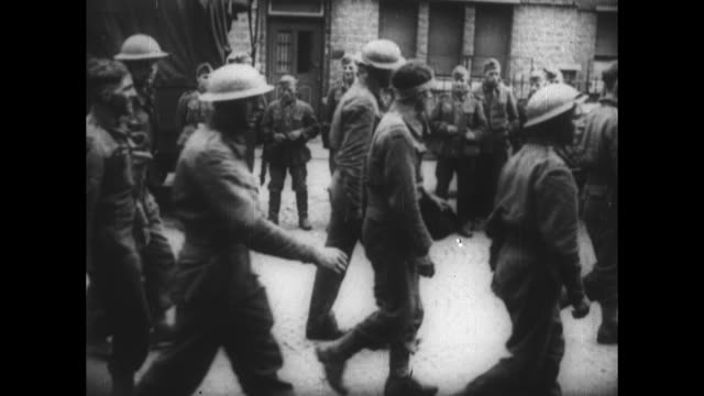 [from german film confiscated by canadian government] civilians and german soldiers stand on sidewalk watching captured british soldiers marching... - prisoner video stock e b–roll