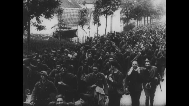 [from german film confiscated by canadian government] vs hundreds of allied prisoners of war march along road carrying bedrolls satchels some wave at... - arrendersi video stock e b–roll