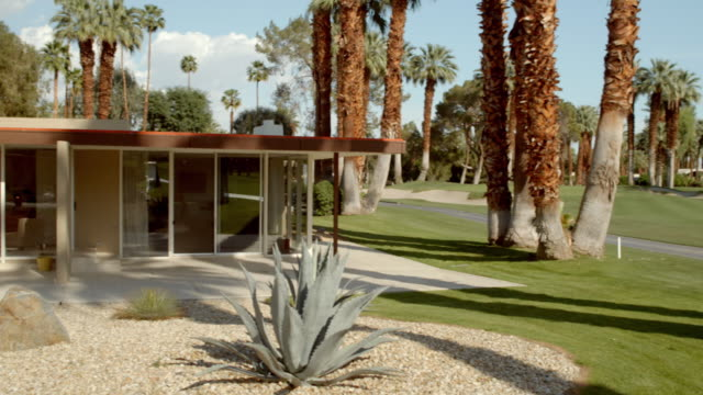 PAN from green golf course fairway with palm trees to mid-century modern home with flat roof and a large cantilevered overhang supported by one square steel post in typical Desert Modern architectural style