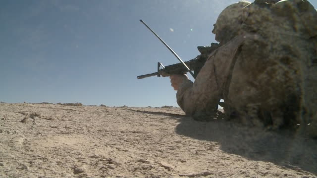 from ground of us army soldier lying on ground and shooting rounds during war in afghanistan - afghan national army stock videos & royalty-free footage