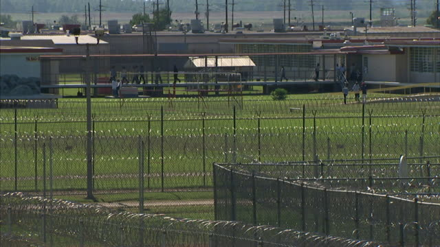 WS Prisoners walking fenced enclosed breezeway between buildings w/ layers of fencing looped razor wire beyond prison yard FG Incarceration not jail...