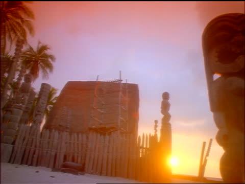 pan from hawaiian tiki god statues with sunset + ocean in background / puu honua o honaunau, island of hawaii - hawaiian culture stock videos & royalty-free footage