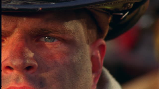 HANDHELD EXTREME CLOSE UP TILT DOWN from helmet to dirty face of serious firefighter\n