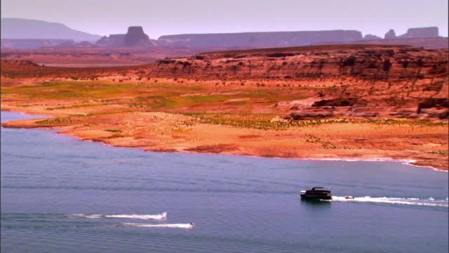 zo from house boat pulling speed boat across lake powell and wide vista of arizona desert scenery in  glen canyon national recreation area/ page, arizona, usa - lake powell stock videos & royalty-free footage