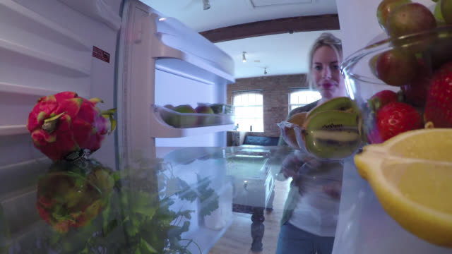 from inside a fridge, a woman places down a slice of pie - one mid adult woman only stock videos & royalty-free footage