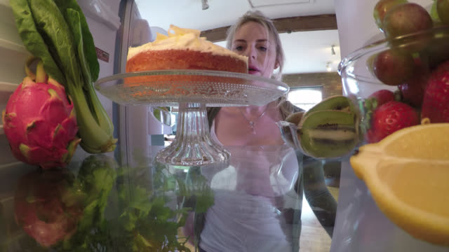 from inside a fridge, a woman sneakily takes a bite out of a cake - unhealthy eating stock videos & royalty-free footage
