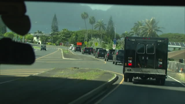 from inside car. car drives on road in hawaii behind truck and long row of black suv's, president barack obama's motorcade. car's turn to pass under... - median nerve stock videos & royalty-free footage