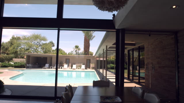 ws ds from inside living room to swimming pool and entry colonnade of mid-century modern home - palm springs california pool stock videos & royalty-free footage