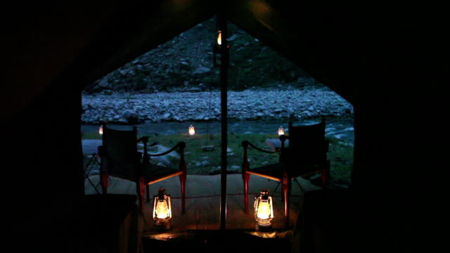 POV from inside safari style tent of two chairs and two beds with lanterns and river in background.