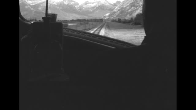 from inside train cab as train moves on track through an area of the canadian rockies / side shot engineer drives the train / his hand on the... - throttle stock videos & royalty-free footage