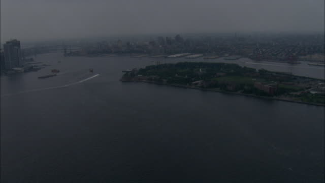 from landing skids of helicopter flying over new york harbor, governors island w/mouth of hudson river, east river and high-rise... - croazia video stock e b–roll