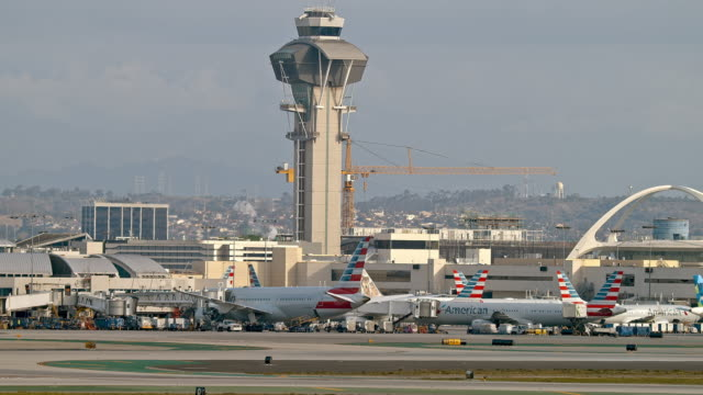 ls pan from lax air traffic control tower to iconic theme building built in 1961 and airport terminals with multiple american airlines planes taxiing in and out of terminal gates to and from airport runways - lax airport stock videos & royalty-free footage