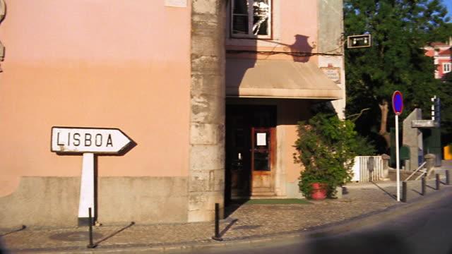"vídeos y material grabado en eventos de stock de pan from ""lisboa"" arrow sign against yellow building to street in town with trees + buildings in background - sign"