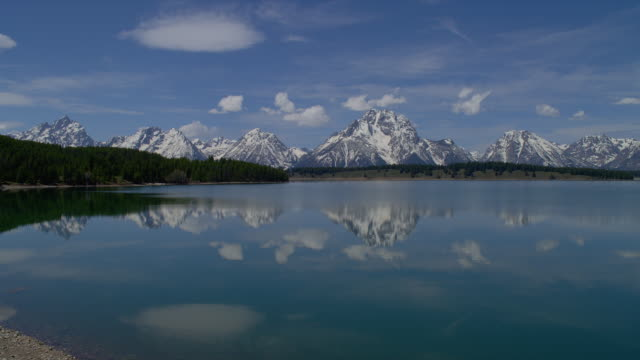 zoom in from long to wide shot few clouds in blue sky above mt moran and teton range with snake river in foreground, grand teton national park, wyoming - mt moran stock videos & royalty-free footage