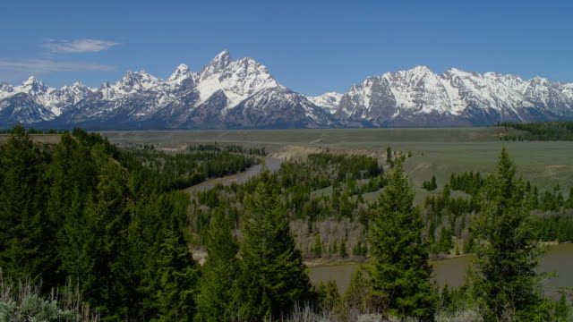 HIGH ANGLE ZOOM IN from LONG to WIDE SHOT snowy Grand Teton and Teton Range with green plain, trees, and Snake River in foreground, Grand Teton National Park, Wyoming
