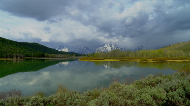 zoom in from long to wide shot storm clouds partially obscuring mt moran and teton range with snake river and forest in foreground, grand teton national park, wyoming - mt moran stock videos & royalty-free footage
