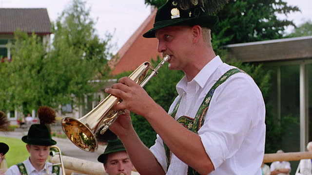 pan from man in german costume playing trumpet to other musicians / bad kohlgrub, bavaria, germany - musiker stock-videos und b-roll-filmmaterial