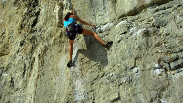 tu from man on beach belaying to woman climbing rock face / krabi, thailand - rock face stock videos & royalty-free footage
