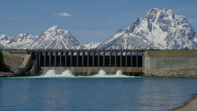 zoom out from medium to wide shot jackson lake dam with snowy mt moran and teton range in background, grand teton national park, wyoming - mt moran stock videos & royalty-free footage