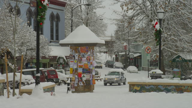 zoom out from medium to wide shot people and traffic on snowy street during holidays in downtown ashland, oregon - generic location stock videos & royalty-free footage