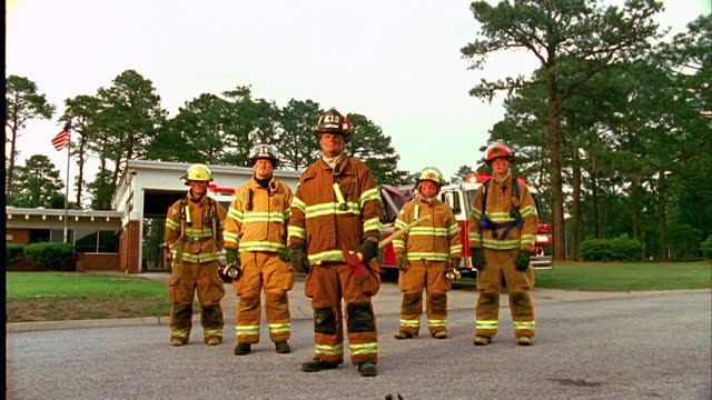 LOW ANGLE DOLLY from MEDIUM to WIDE SHOT portrait group of firefighters in gear standing in front of fire station\n
