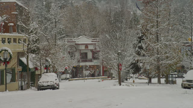 ZOOM OUT from MEDIUM to WIDE SHOT snow falls on snowy street decorated for holidays in downtown Ashland, Oregon