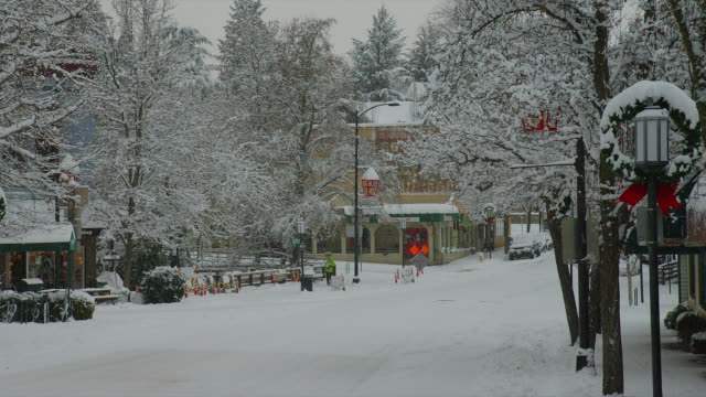 ZOOM OUT from MEDIUM to WIDE SHOT two cars and one person on snowy street decorated for holidays during snowfall in downtown Ashland, Oregon