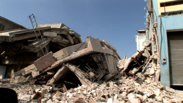stockvideo's en b-roll-footage met pov from moving car dilapidated buildings and destruction left around haiti after the earthquake / view of damaged church and christ on the cross /... - 2010