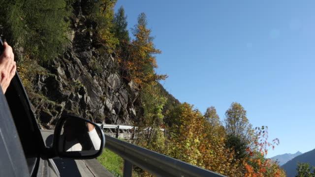 vídeos y material grabado en eventos de stock de pov from moving car on mountain road, with couple seated - retrovisor exterior